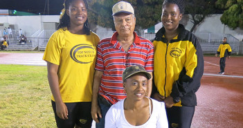 """Former BVIAA President Johnny Hassan, is flanked by Shot Putters and twin sisters Trevia and Tynelle Gumbs, the first two females to throw over 12.00m in the same competition and official Roslyn Gilbert, who sits in the chair with the table Hassan donated.  PHOTO CREDIT:  Dean """"The Sportsman"""" Greenaway"""