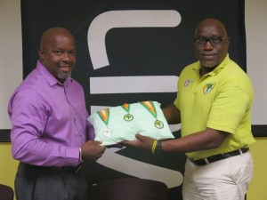 LIME BVI Manager Sean Auguste presents a sample of the medals athletes will win during the weekend championships to BVI Athletics Association President Dean Greenaway