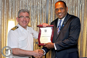 Minister for Communications and Works Honourable Mark Vanterpool presents a plaque to Carnival Sunshine's Captain Roberto Liotta during a ceremony to commemorate the ship's first call to the cruise pier on April 23, 2014. (Photo credit: GIS/ Mr. Ronnielle Frazer)