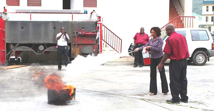 Sub Officer Geraldo Barry keeps a close watch as one of the teachers demonstrates the use of the fire extinguisher during fire suppression training, Photo Credit: Department of disaster Management.