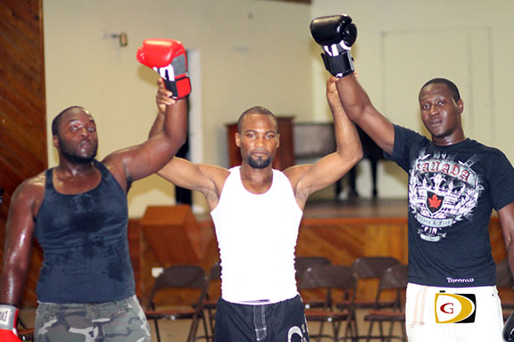 Coach, referee and promoter Julan Brown, center with Arthur Corion, left and Travis Jack following their bout.