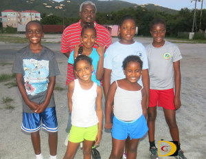 Coach Elsworth Phillip with some home based members of the 2014 OECS Swimming team