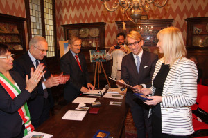 At left, applauding: Legnago's Mayor, Clara Scapin; St. Gabriel award President, Senator Gianni Fontana. Far right: general  vice-consul of Poland Bartosz Skwarczynski, and head of the  philatelic and marketing agencies of the Polish Posts Agnieszka  Kloda-Debska proudly holding, respectively, the Diploma of the  St. Gabriel International Award for Best Religious Stamp, 2015,  and the artistic sterling silver plaque.