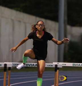 """Lakeisha """"Mimi"""" Warner clears the eight hurdle, en route to running a personal best of 1:00.00."""
