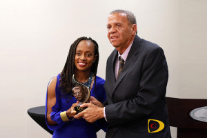 Sprinter Tahesia Harrigan-Scott, left, presents the IOC's Pierre de Coubertin Trophy to BVI Athletics Association Founding member Rey O'Neal, during a tribute dinner held by the BVI Olympic Committee.