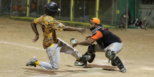 The Pirates' Nicos Penn is tagged out at home plate by Power Outage's Kyle Callwood