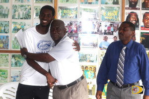 Kyron McMaster, left, is congratulated by his coach Dag Samuels after committing to Florida, as his father Anthony looks on