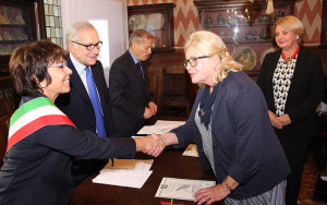 Legnago's Mayor Clara Scapin and St. Gabriel Award chairman Gianni Fontana present Zelika Corak of Croatia Posts the 2016 Award, looking on at far right Consul General Nevenka Gradinic