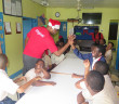 Digicel General Manager, Kevin Gordon high fives students at the Eslyn Henley Richiez Learning Center during a gift giving extravaganza on Monday