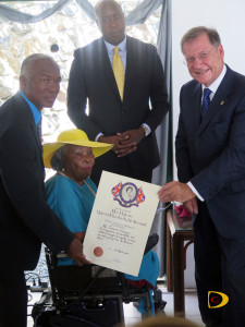 "Terry ""Chino"" Chinnery, left, and his sponsors Eileen Parsons and Hon. Myron Walwyn, as he's presented the certificate by Governor John S. Duncan, after receiving the BVI Badge of Honor for his work in Softball."