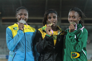 Nelda Huggins, right join her counterparts from the Bahamas and Jamaica in tasting their U18 Girls 100m medal