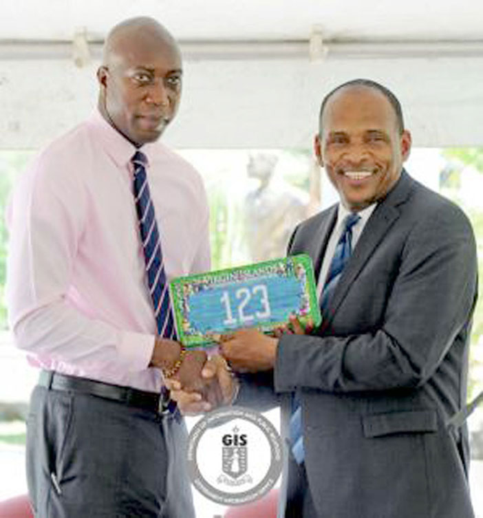 Minister for Communications and Works, Honourbale Mark Vanterpool passed the commemorative licence plate to Minister for Education and Culture Honourable Myron Walwyn
