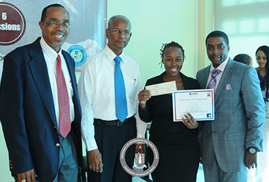 Premier and Minister of Finance, Dr. the Honourable D. Orlando Smith OBE is pictured here with Director of Trade and Consumer Affairs, Mr. Maxwell George and Power Move Facilitator Mr. Devin Robinson as they recognised the Capstone Top Student and PMAC Graduate, Mrs. Akeema Crabbe. (Photo Credit: Ronnielle Frazer).
