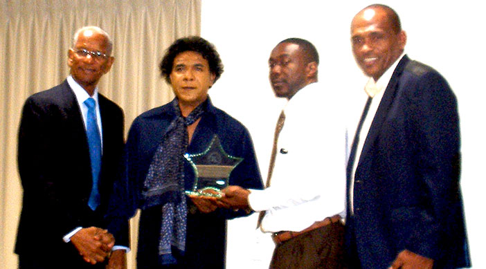 The Island Sun Executive Editor (1985 to date) Vernon W. Pickering shaking hand with British Virgin Islands Premier and Minister of Finance Dr. the Honourable D. Orlando Smith after receiving the TRC Award. At far right Communications and Works Minister Hon. Mark Vanterpool.