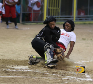 Pythons catcher Jelissa Potter blocks home plate to prevent the Hawks' Shanika Forbes from scoring during Sunday's 13-9 victory, extending their winning streak to 62 games.