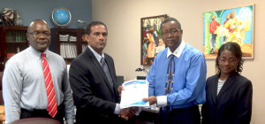 Chairman of the Minimum Wage Advisory Committee, Mr. Simon Potter (3rd from left) handed over the official document of the Territory's Minimum Wage Report to Deputy Premier and Minister for Natural Resources and Labour, Dr. the Honourable Kedrick Pickering (2nd from left) on Friday, July, 24, following the completion of its six month mandate (GIS Photo)