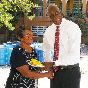 Ms. Phylis George (representing the late Dr. Pearl Varlack) receiving gift of gratitude from Minister for Education & Culture Hon. Myron Walwyn
