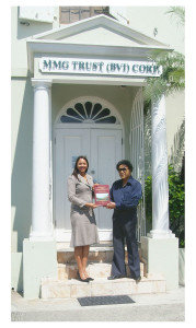 """Miss Fanny Evans, Executive Director and General Manager of MMG Trust (BVI) Corp. and Vernon Pickering holding a copy of his book """"Early History of the British Virgin Islands"""", 4th edition at the headquarters of the company at Pasea, Road Town. [Paul's Photos]"""