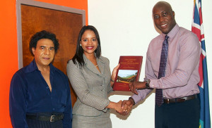 """Miss Fanny Evans, Executive Director and General Manager of MMG Trust (BVI) Corp. presents a copy of the book """"Early History of the British Virgin Islands"""", 4th edition, to Minister for Education & Culture, Honourable Myron Walwyn at the Ministry. At left is the author of the BVI's best-selling book Mr. Vernon Pickering. [Paul's Photo]"""