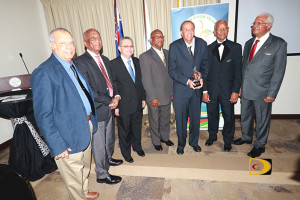 Rey O'Neal, 5th right, is surrounded by colleagues from 43 years, Johnny Hassan, left, Austin Sealey, Victor Lopez, Keith Joseph, Premier Dr. Orlando Smith and Amadeo Francis