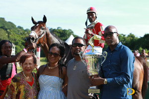 "Sports Minister Hon. Myron Walwyn presents the Virgin Islands Classic trophy to St. Moose's owner, James ""Bubba"" Bates, after winning the $20,000 feature race, as BVI Horse Racing Association president, Patsy Lake, left, looks on"