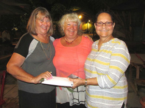 All smiles: Quiz Master Julie Cooper (middle) with Judith Charles (right) and Gayle Lettsome Photo by Astrid C. Wenzke