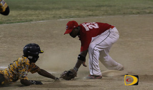 Tramore Fraser of the Pirates, left, is tagged out by the Reds third baseman after sliding past the bag