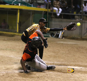 "Power Outage's Tecius Frett slides home as the ball eludes Pirates pitcher Allen ""Woodrow"" Smith"
