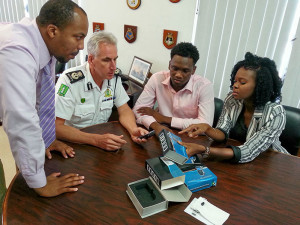 Members of Reaching Out Foundation (l-r) Vice President Chezley Stoddard, President Kevon Lettsome and Advisor Dr. Shakima Stoutt show Commissioner of Police Michael Matthews (centre) the new breathalyzers.