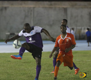 An Islanders player takes control of the ball ahead of his Sugar Boys counterpart