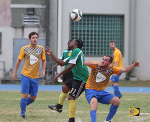 Virgin Gorda United's Kimon Robson heads the ball against the Wolues' Rory Greenan